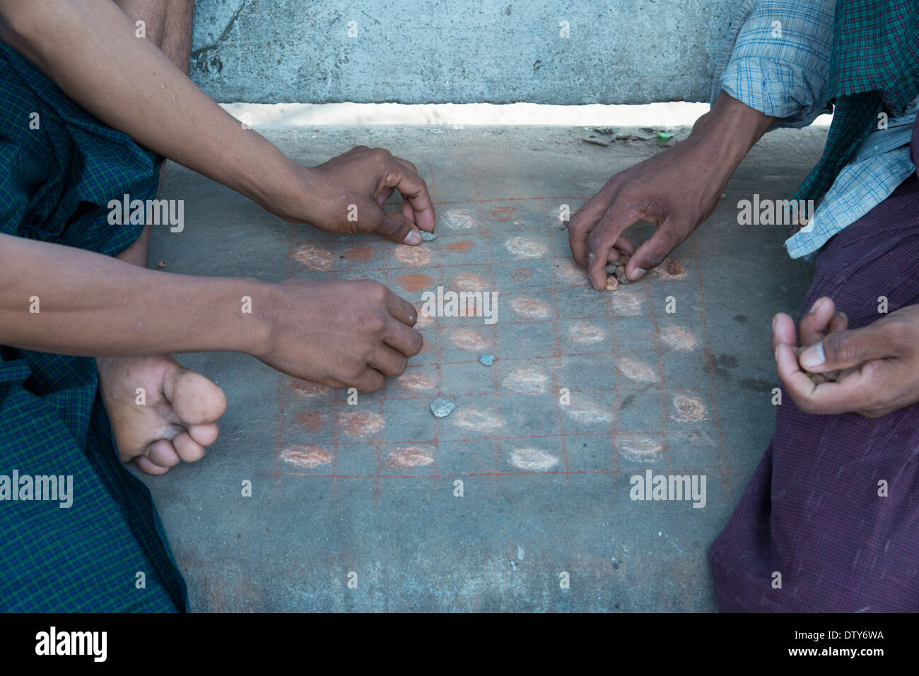 Close up of men playing checkers on an improvised checker board. Yangon. Myanmar (Burma). Stock Photo