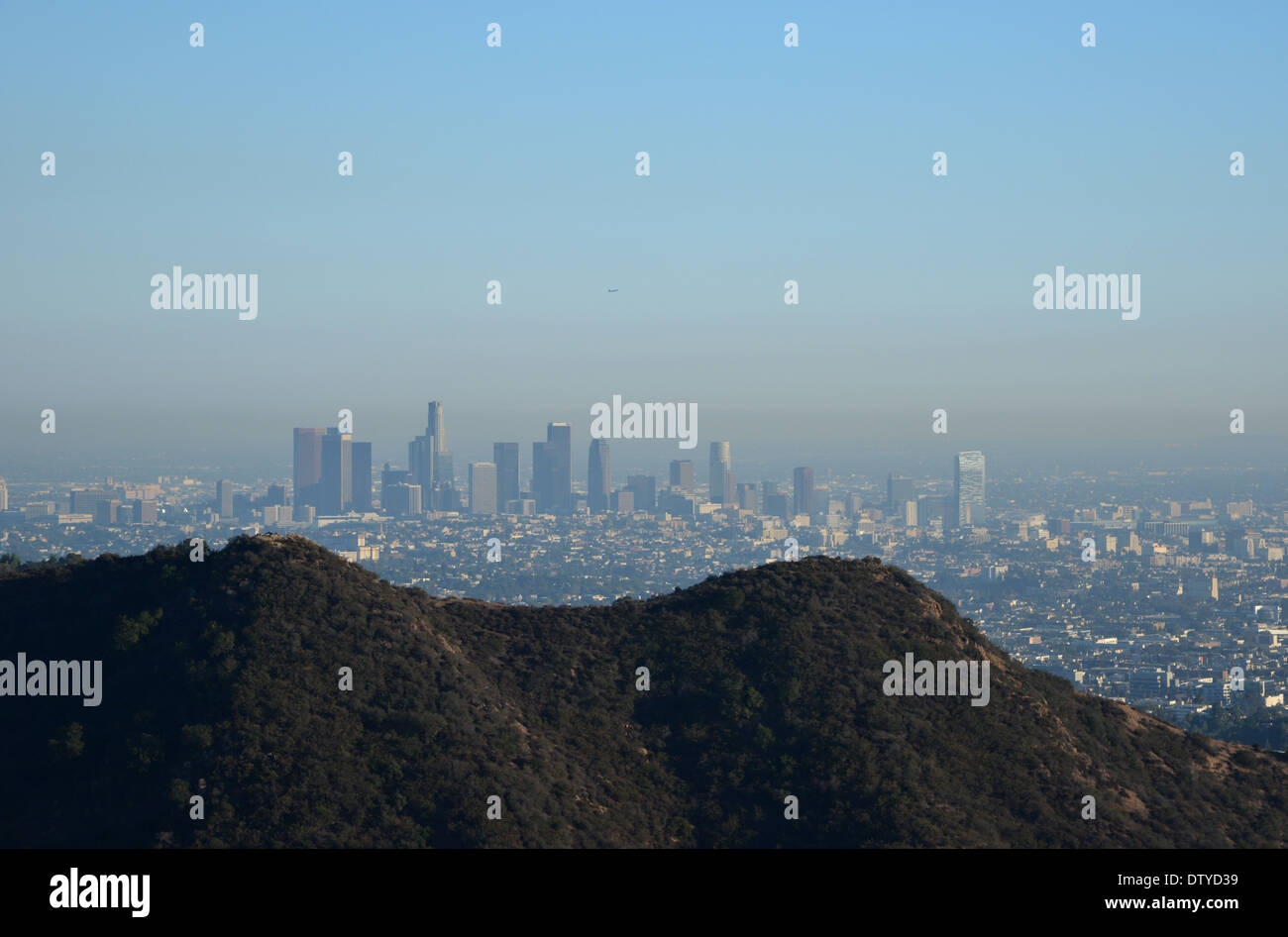 Downtown LA and its smog beneath a blue sky and heat shimmer seen from the Hollywood hills - Stock Image