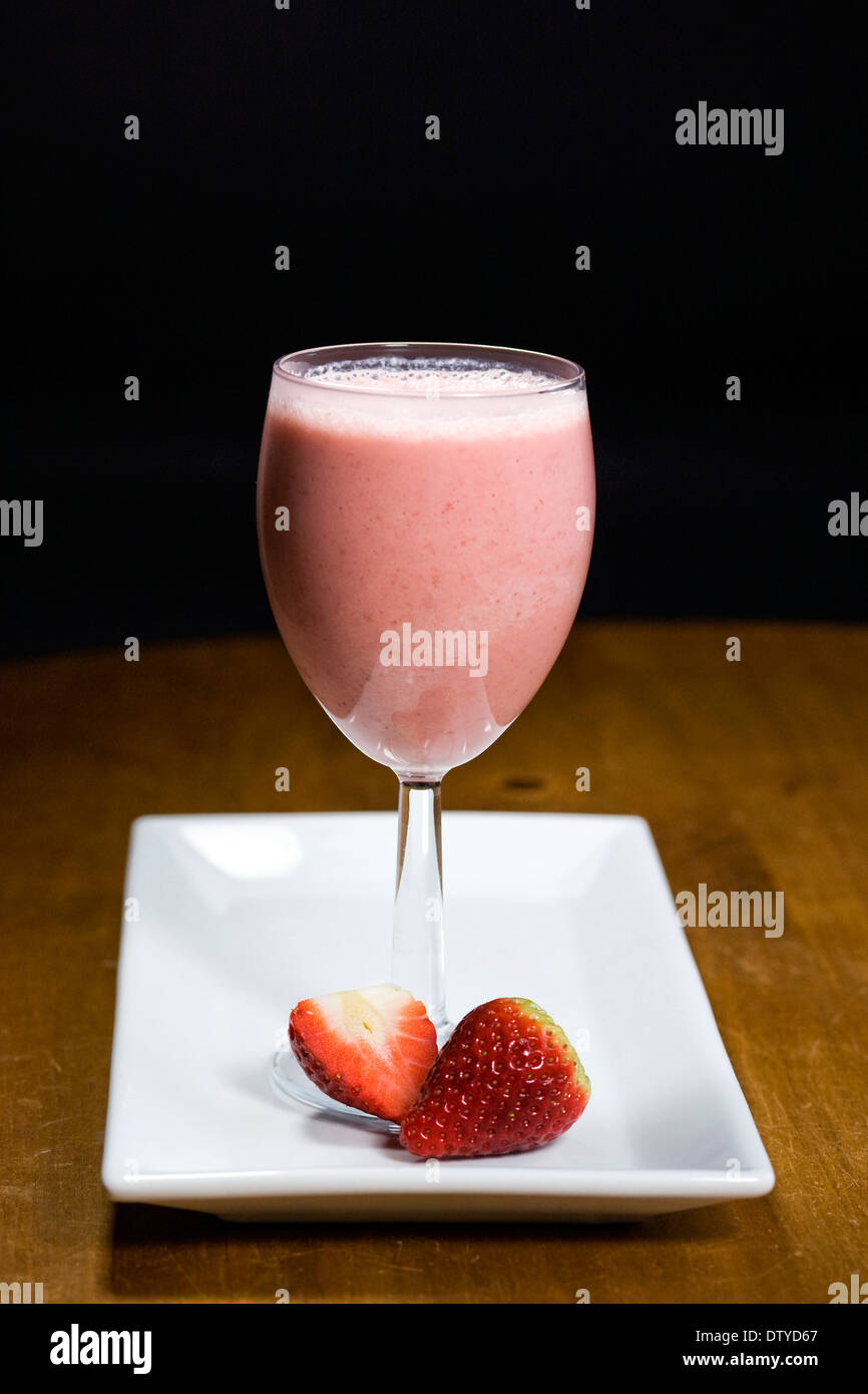 Strawberry smoothie and fruits on a white plate. - Stock Image