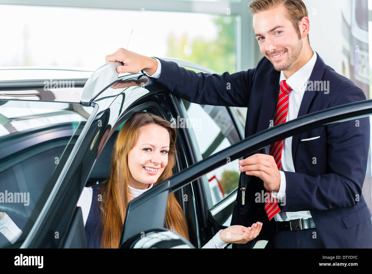 Seller or car salesman and female client or customer in car dealership presenting the interior decoration of new and used cars - Stock Image