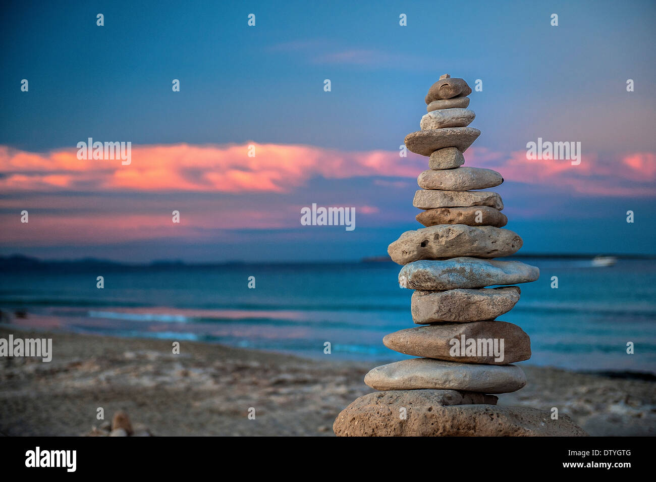 Formentera, Balearic Island. Ses Illetes Beach. Sculptures made ​​of stones at sunset on the Ses Illetes beach. The sky is magic - Stock Image