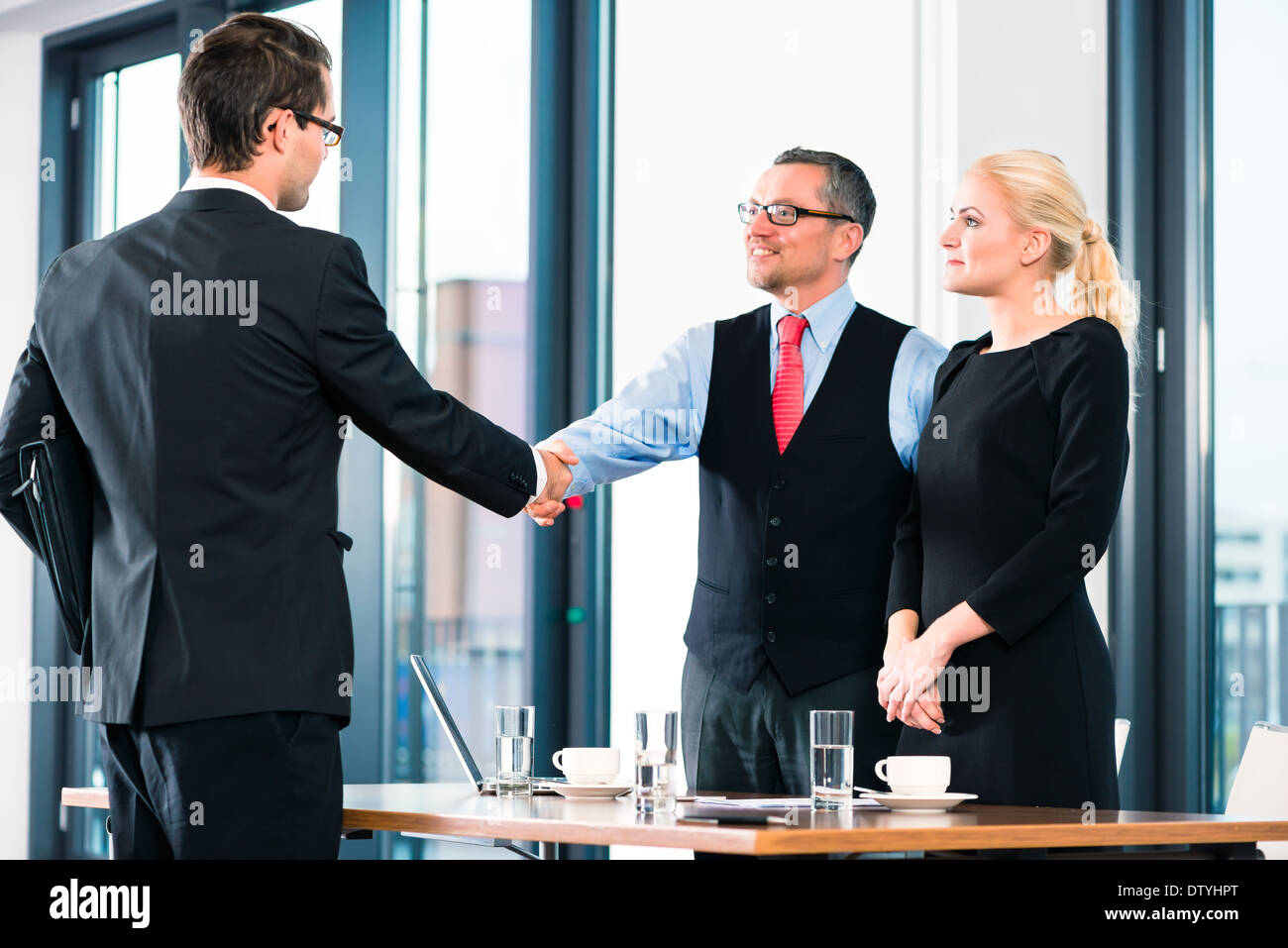Business - young man in job interview for hiring, welcomes, Boss or Senior and his female Assistant in their office - Stock Image