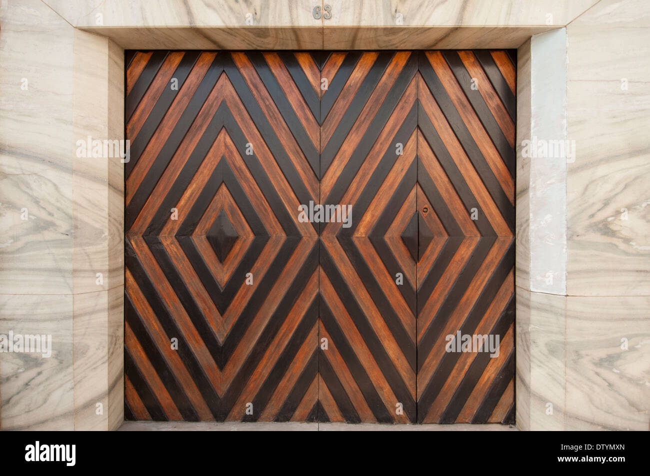 Modern art deco style garage doors set into marble wall portugal