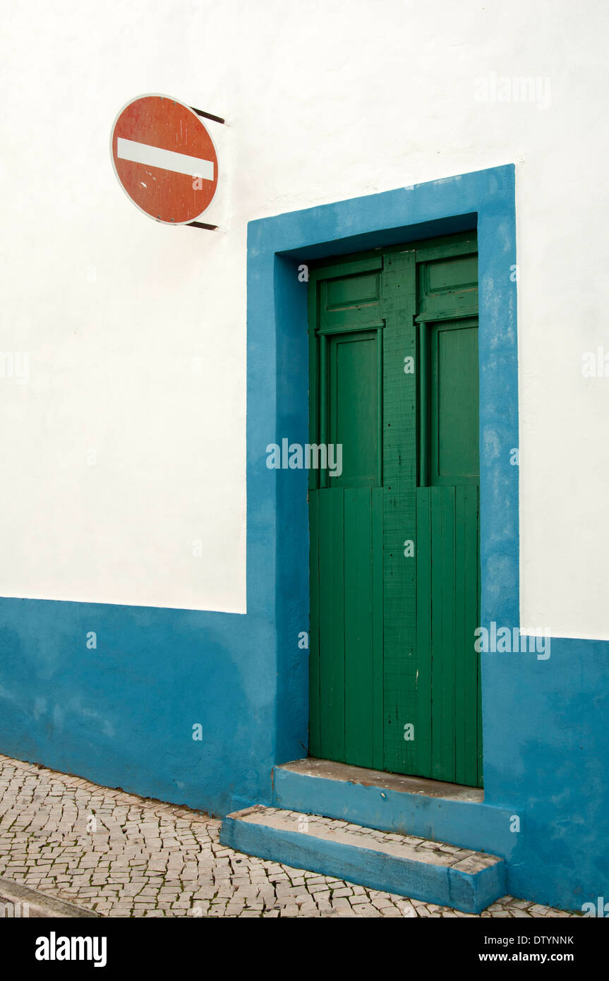 Old green door set in a blue and white wall with a red no entry street sign, Portugal - Stock Image