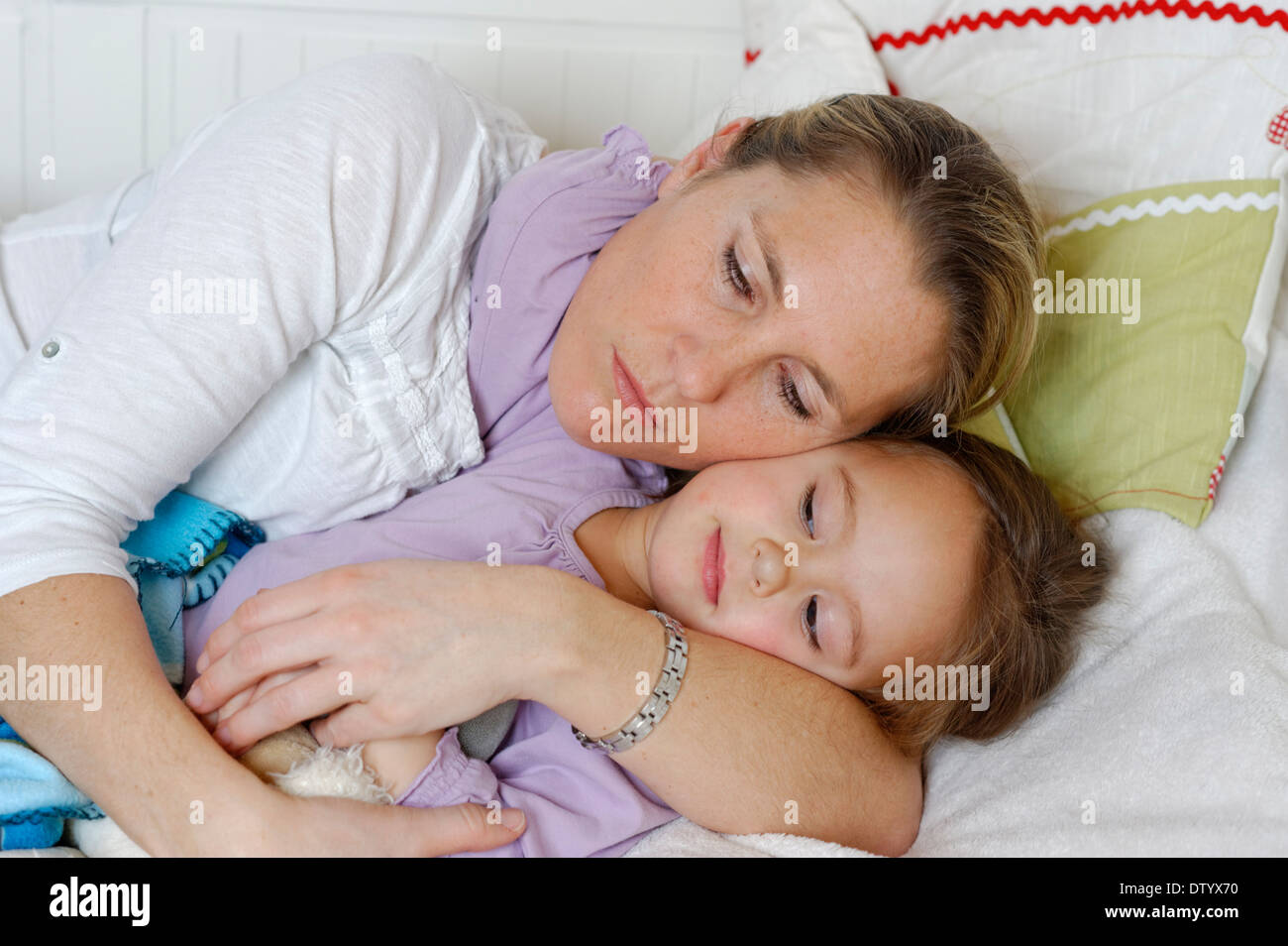 Mother and daughter cuddling in bed, hugging - Stock Image