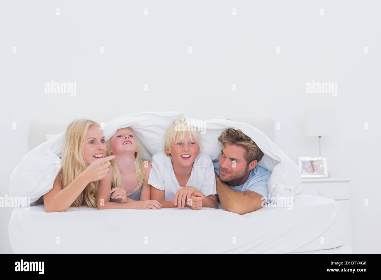 Happy family under the duvet - Stock Image