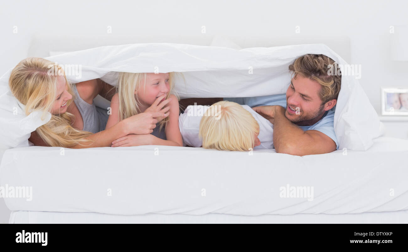 Happy family under the duvet playing - Stock Image