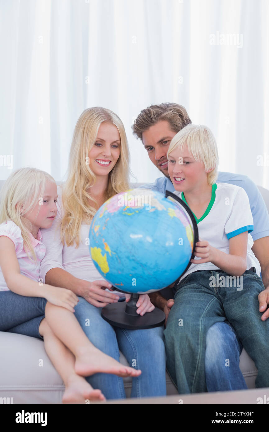 Happy family looking at globe on couch - Stock Image