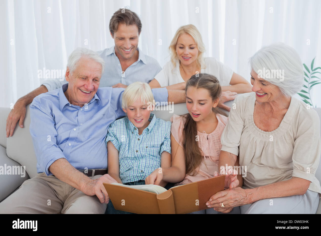 Extended family looking at an album photo - Stock Image