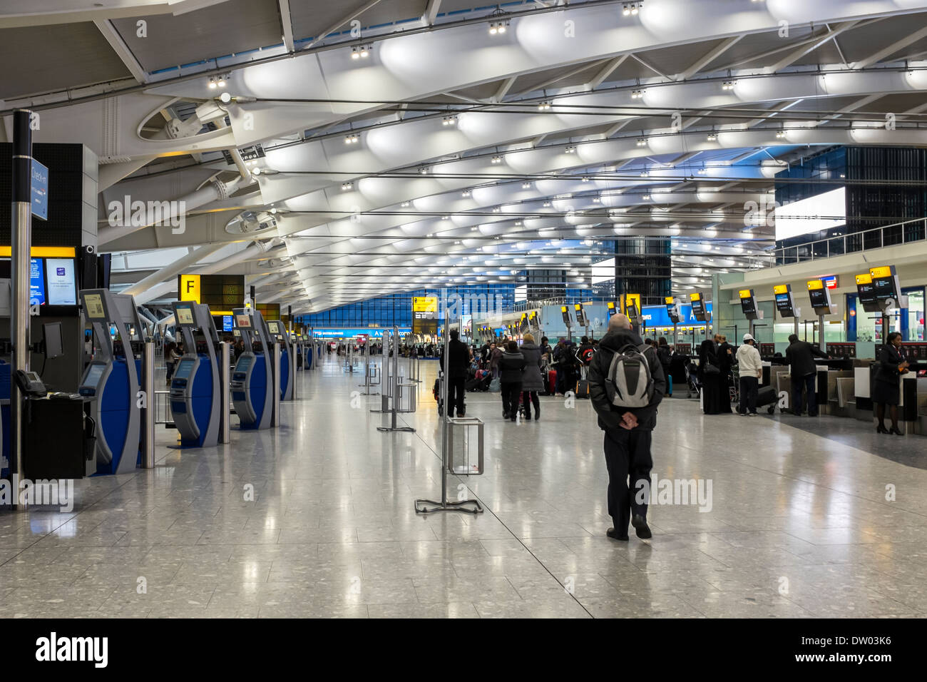 Check in booths and luggage drop off counters in departure hall at Terminal 5 T5, Heathrow Airport, London, UK - Stock Image