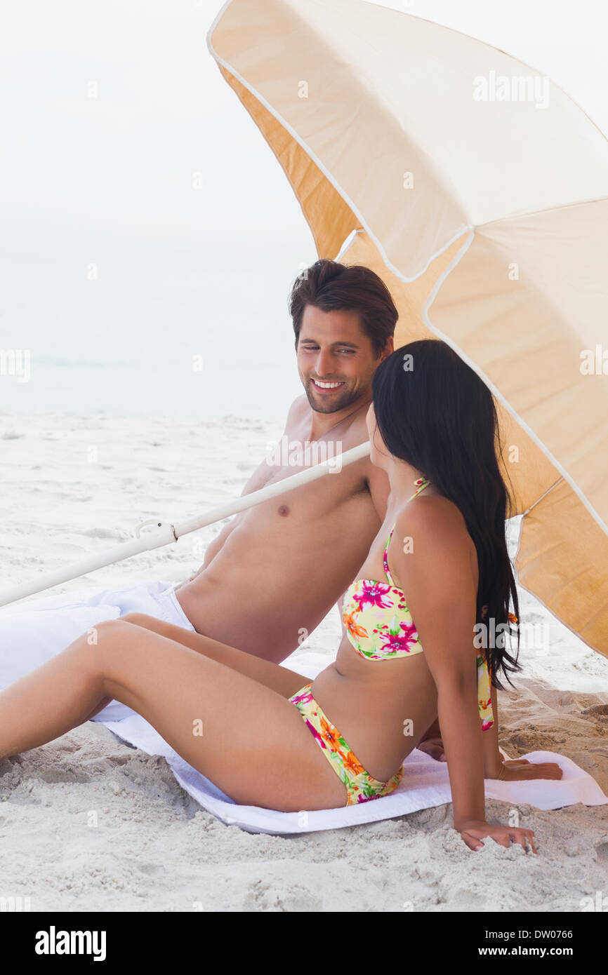 Couple speaking together on beach towel - Stock Image