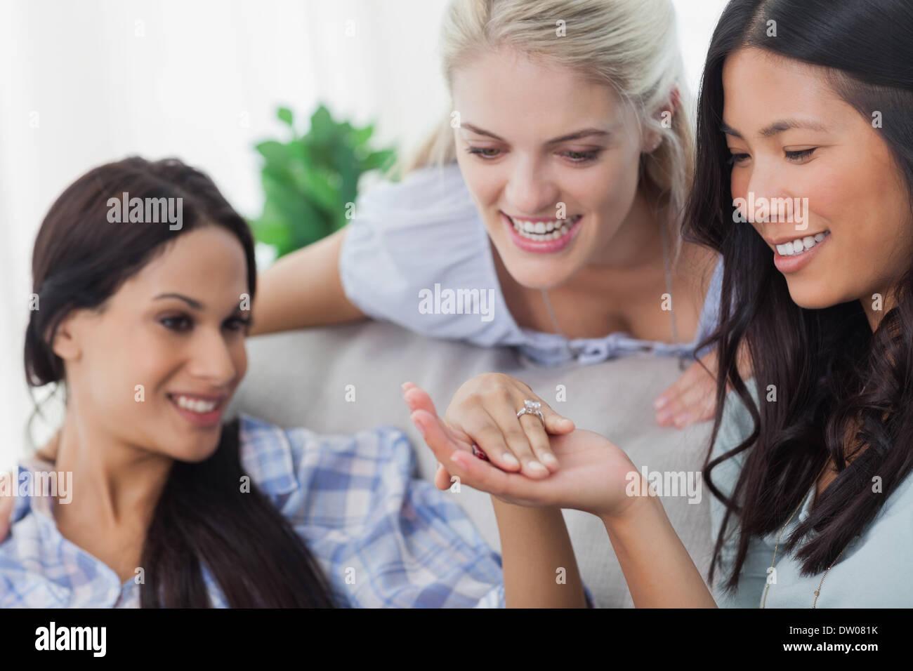 Friends admiring brunettes engagement ring - Stock Image