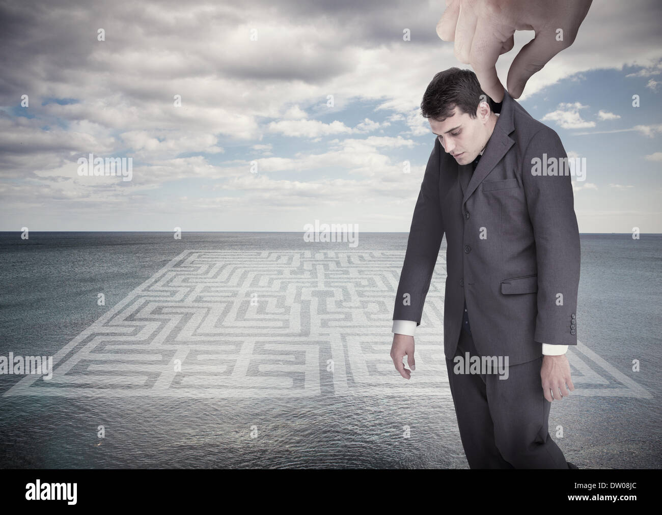 Giant hand dropping off a businessman - Stock Image