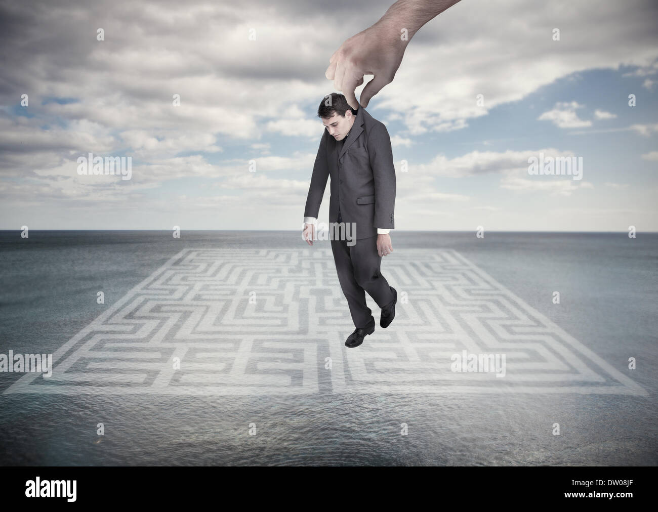 Big hand dropping off a businessman - Stock Image