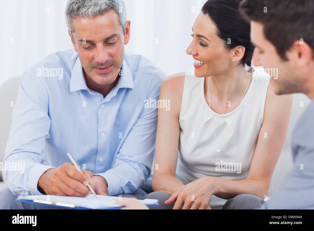 Client signing a contract with wife - Stock Image
