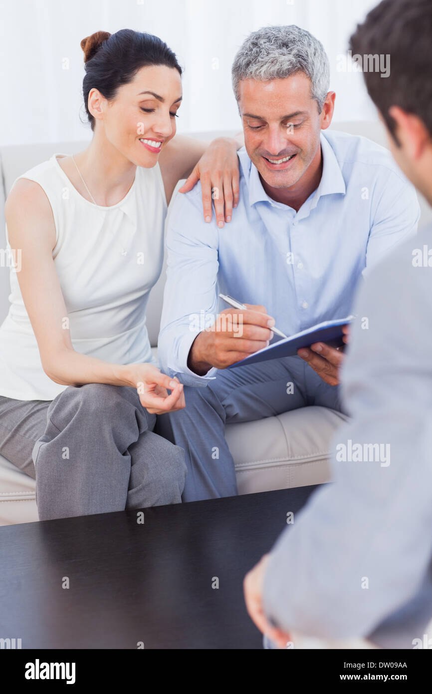 Couple signing salesman contract - Stock Image