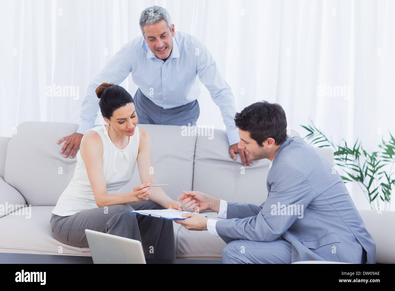 Salesman speaking with customers on couch - Stock Image