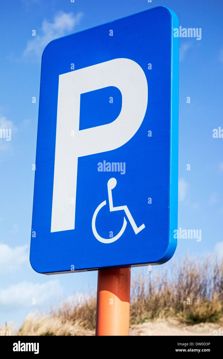 Close up of blue parking sign for disabled people in wheelchair at car park - Stock Image