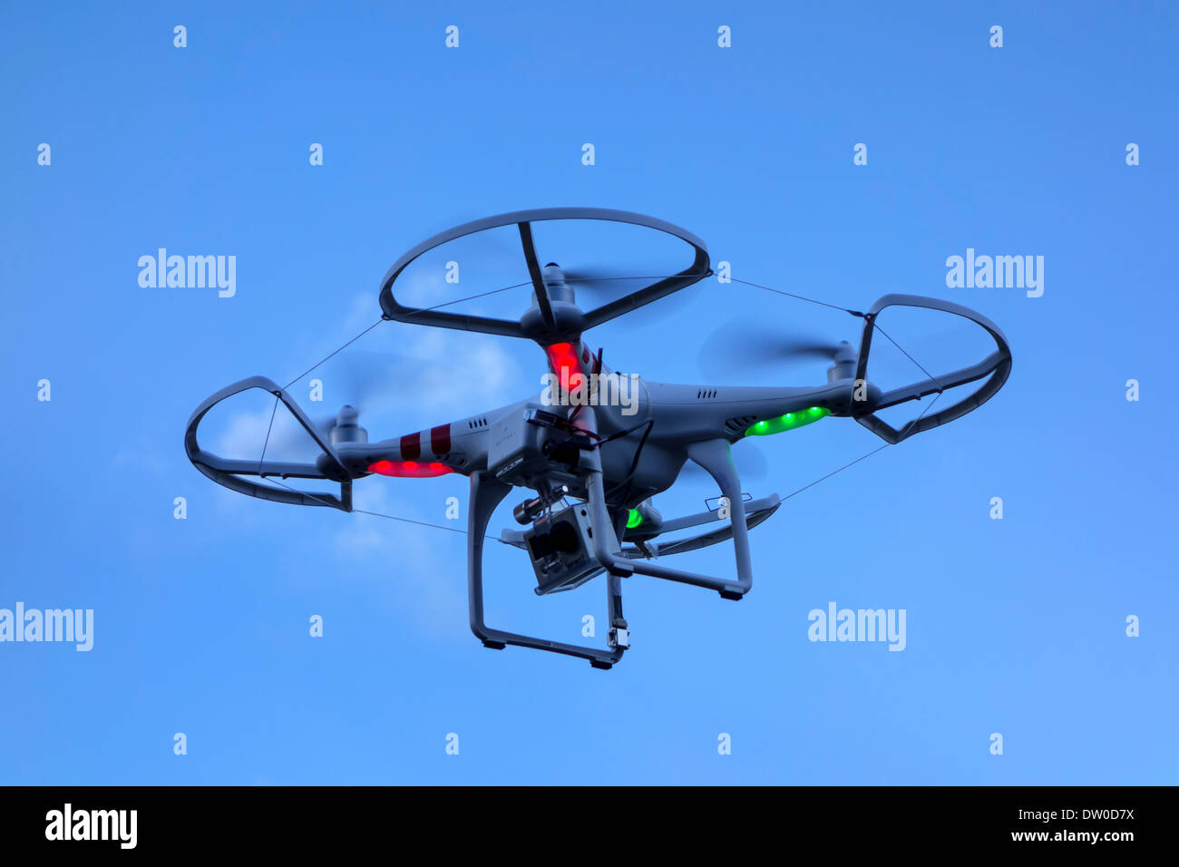 Miniature drone / unmanned aerial vehicle / UAV equipped with camera in flight against blue sky with clouds - Stock Image