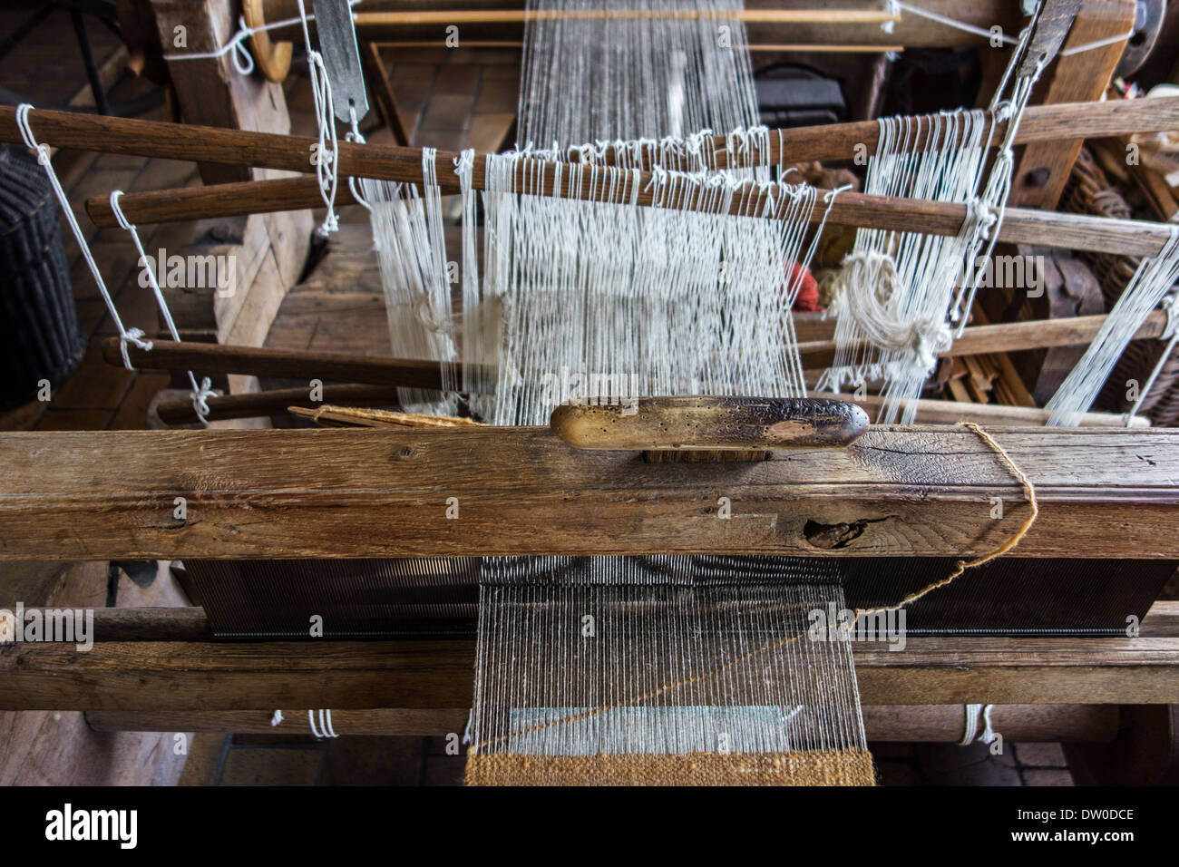 Old wooden eighteenth century hand loom showing heddles at MIAT, industrial archaeology museum, Ghent, Belgium - Stock Image