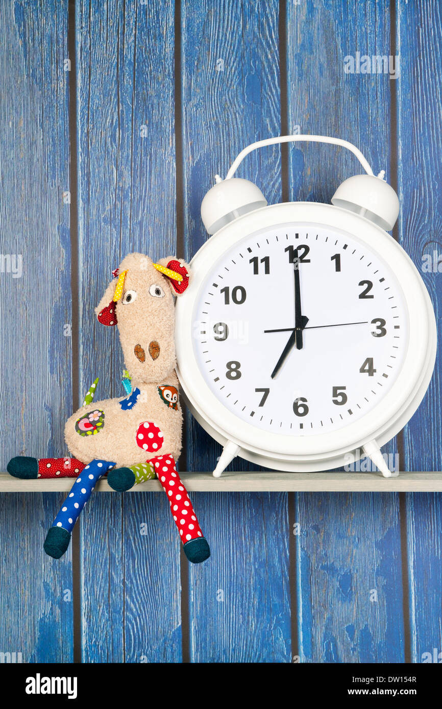 Stuffed animal Giraffe sitting next to alarm clock at seven o'clock isolated over white background - Stock Image