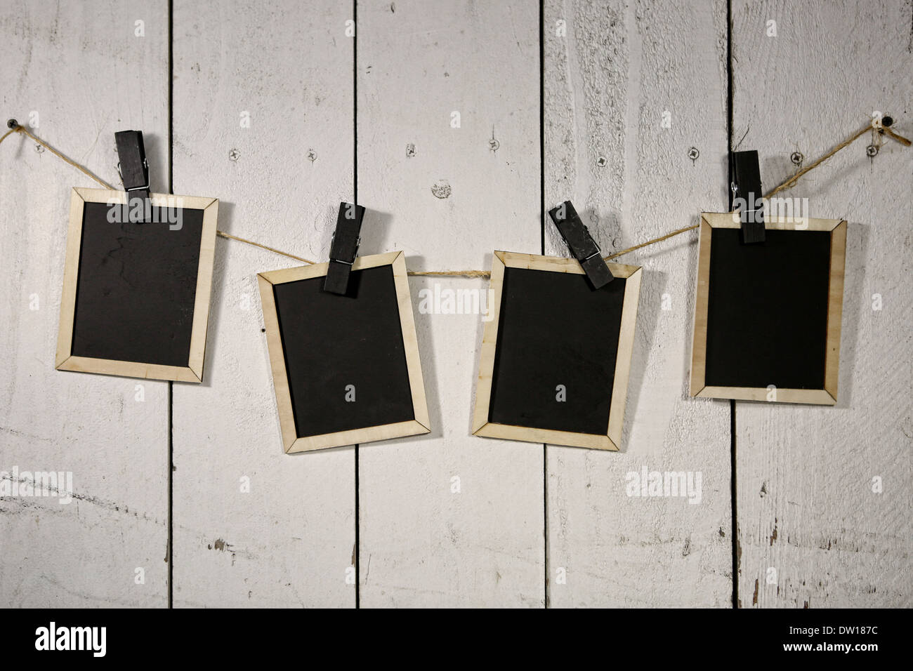 Old Film Looking Chalkboards Hanging on a Rope Held By Clothespins - Stock Image
