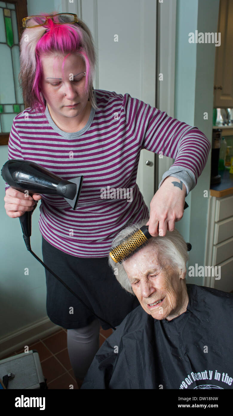 Detroit, Michigan - Hair stylist Jessica Willson, 36, gives a haircut to Dorothy Newell, 100. - Stock Image