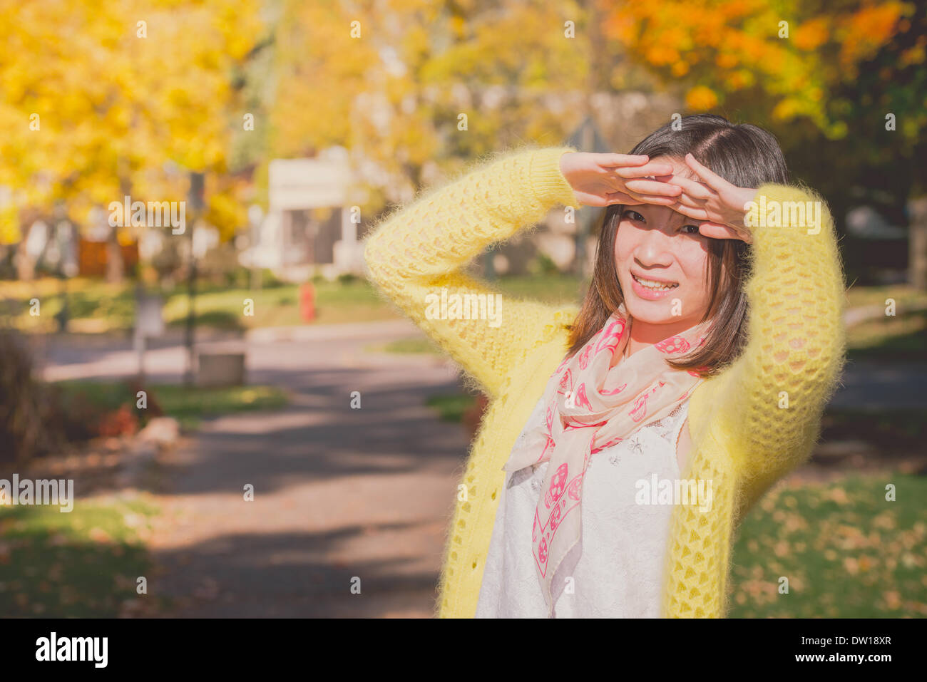 Woman shielding herself from the sun - Stock Image