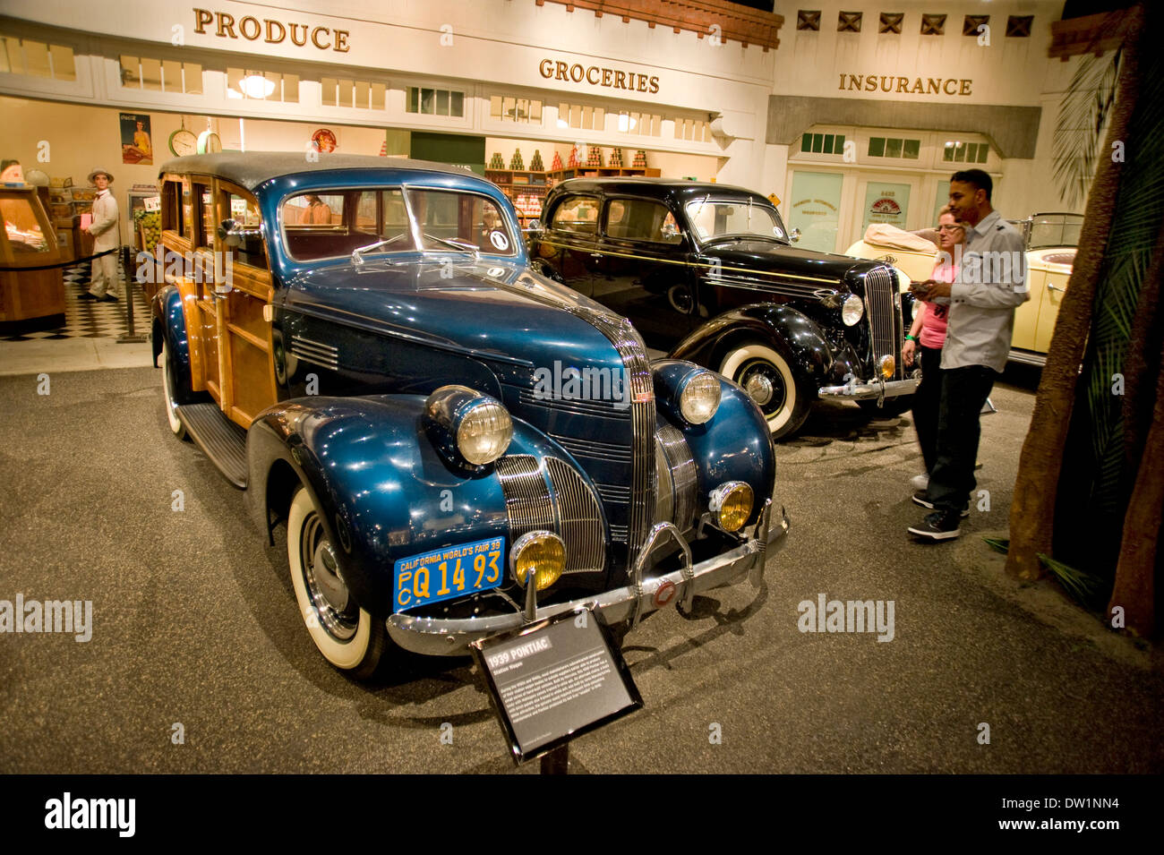 Visitors admiring classic 1939 Pontiac Station wagon on display at the Petersen Automotive Museum in Los Angeles, CA - Stock Image