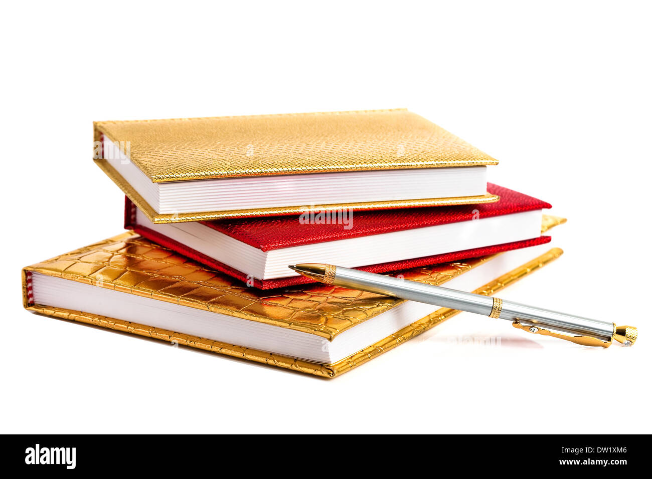 Golden and red notebooks with silver pen - Stock Image