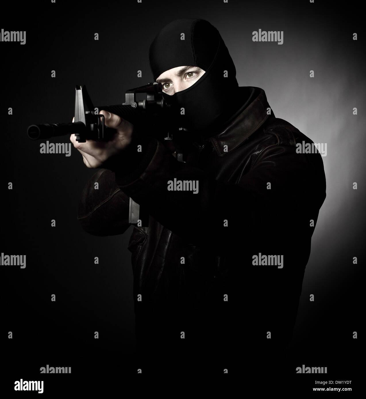 criminal with rifle - Stock Image