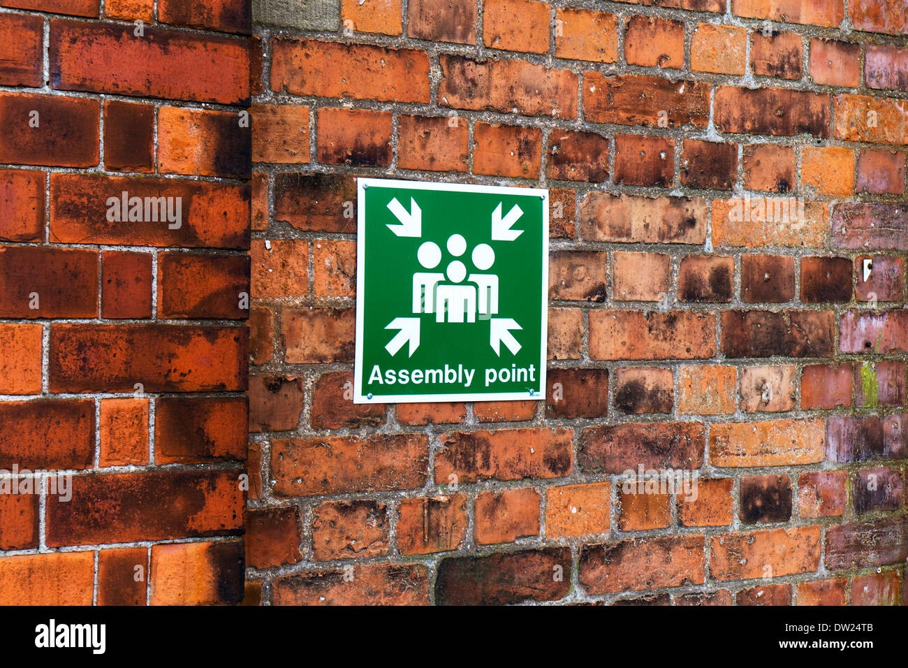Assembly meeting point sign on wall for fire safety - Stock Image