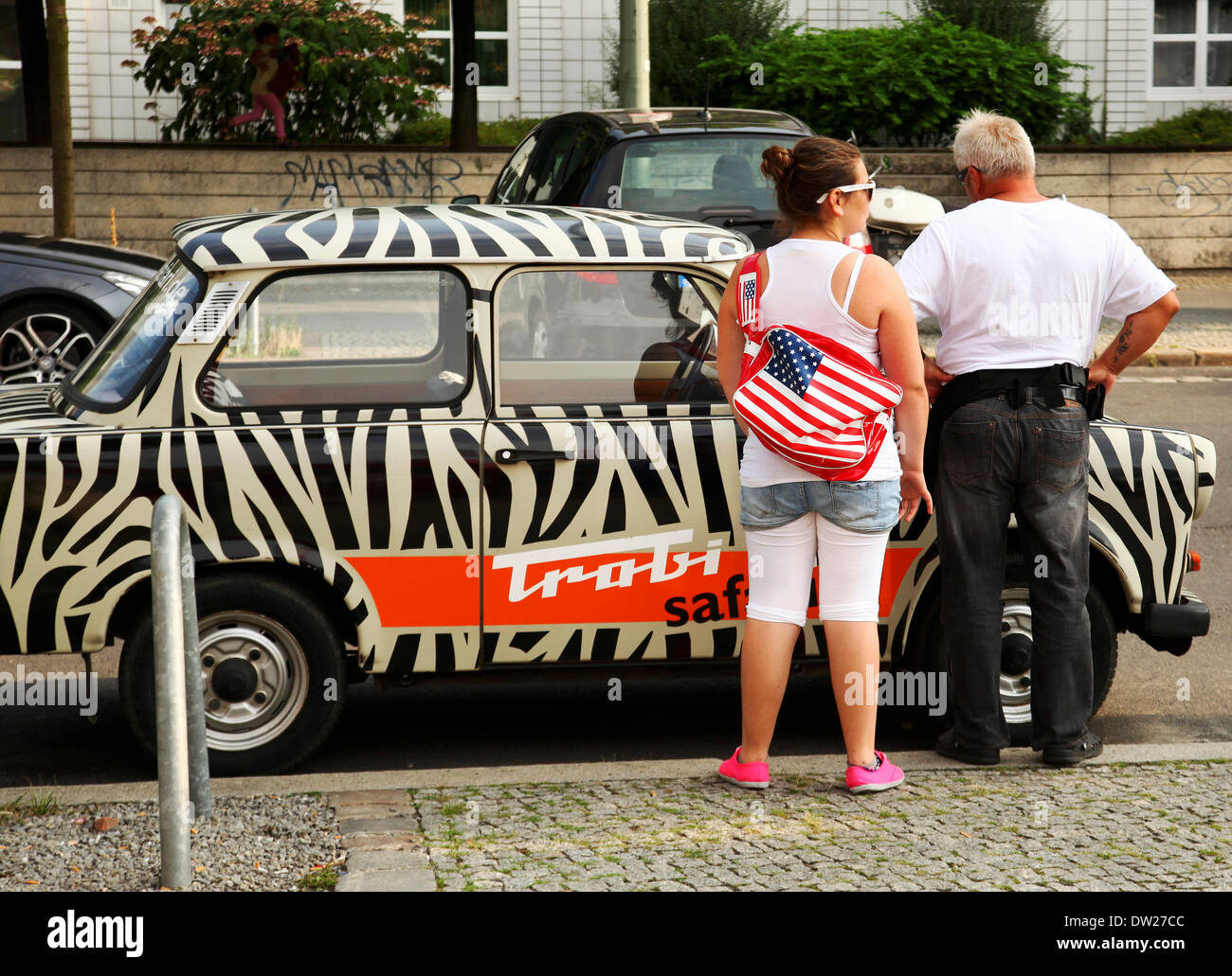 Tourists stand at an East German Trabant car near Checkpoint Charlie in Berlin, August 08, 2013. More and more tourists Stock Photo