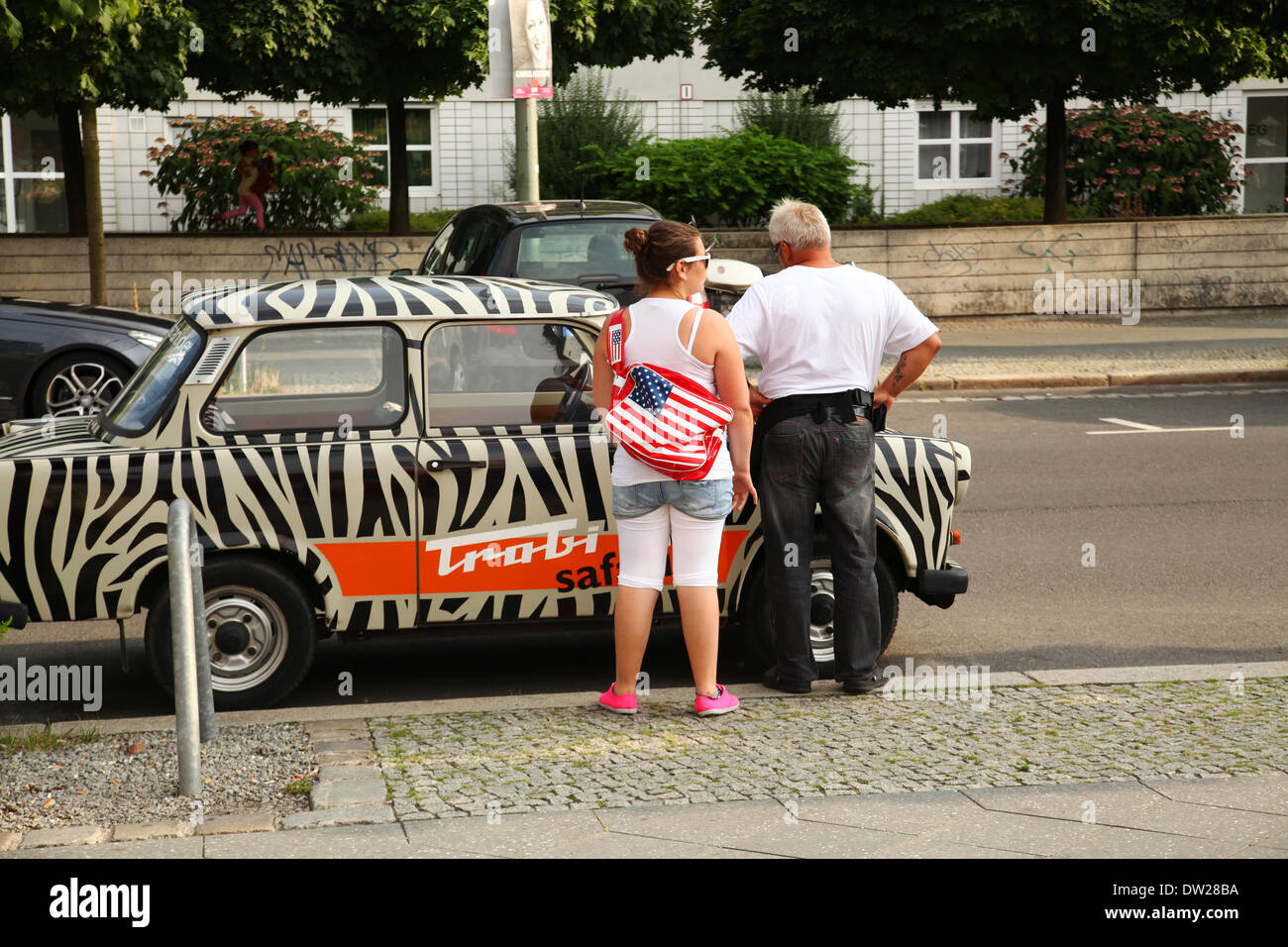 Tourists stand at an East German Trabant car near Checkpoint Charlie in Berlin, August 08, 2013. More and more tourists come to the German capital every year. The photo is part of a series on tourism in Berlin. Photo. Wolfram Steinberg dpa - Stock Image