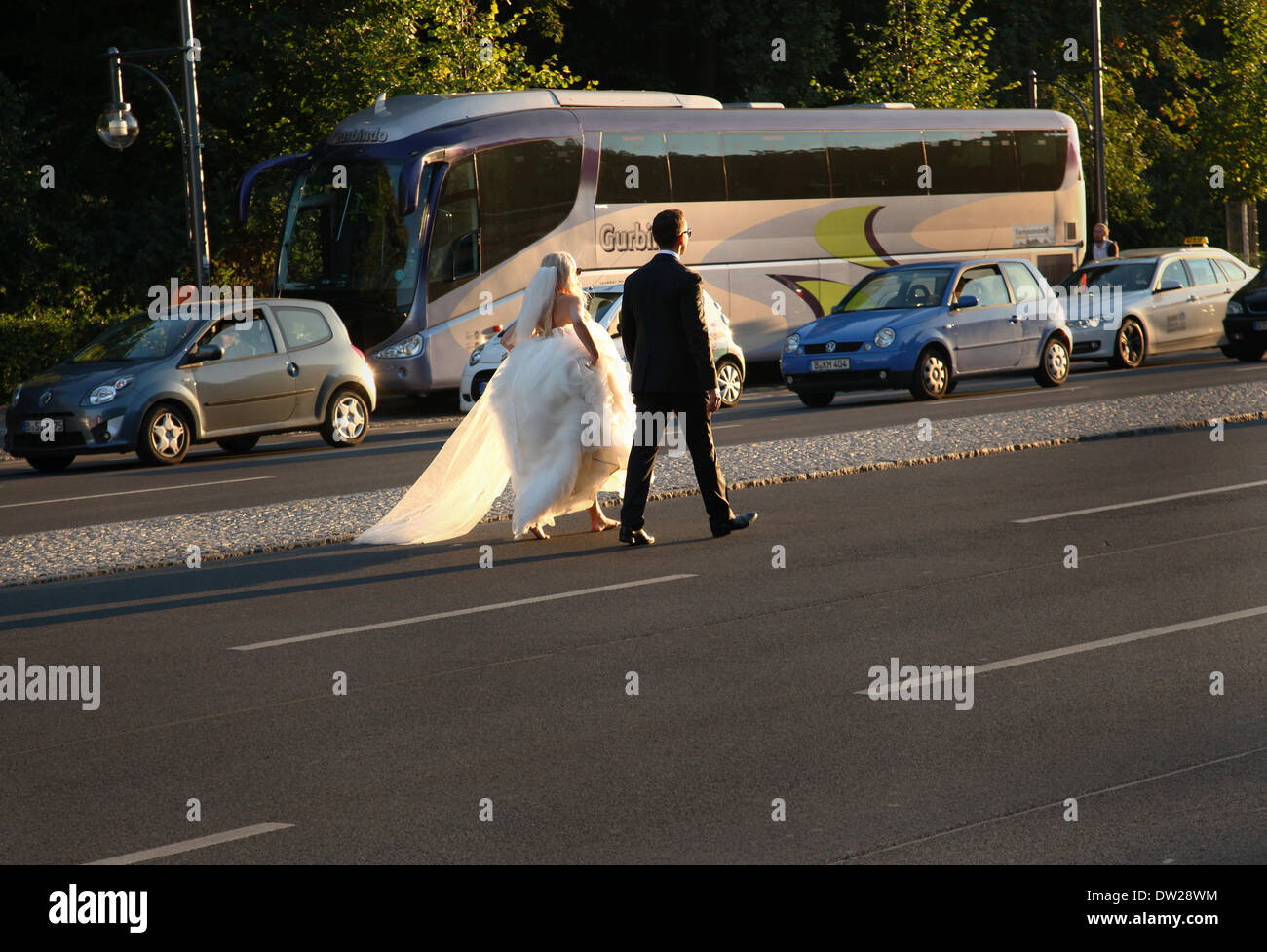 A Polish bridal couple walks on a street at the Brandenburg Gate in Berlin, September 05, 2013. More and more tourists - Stock Photo