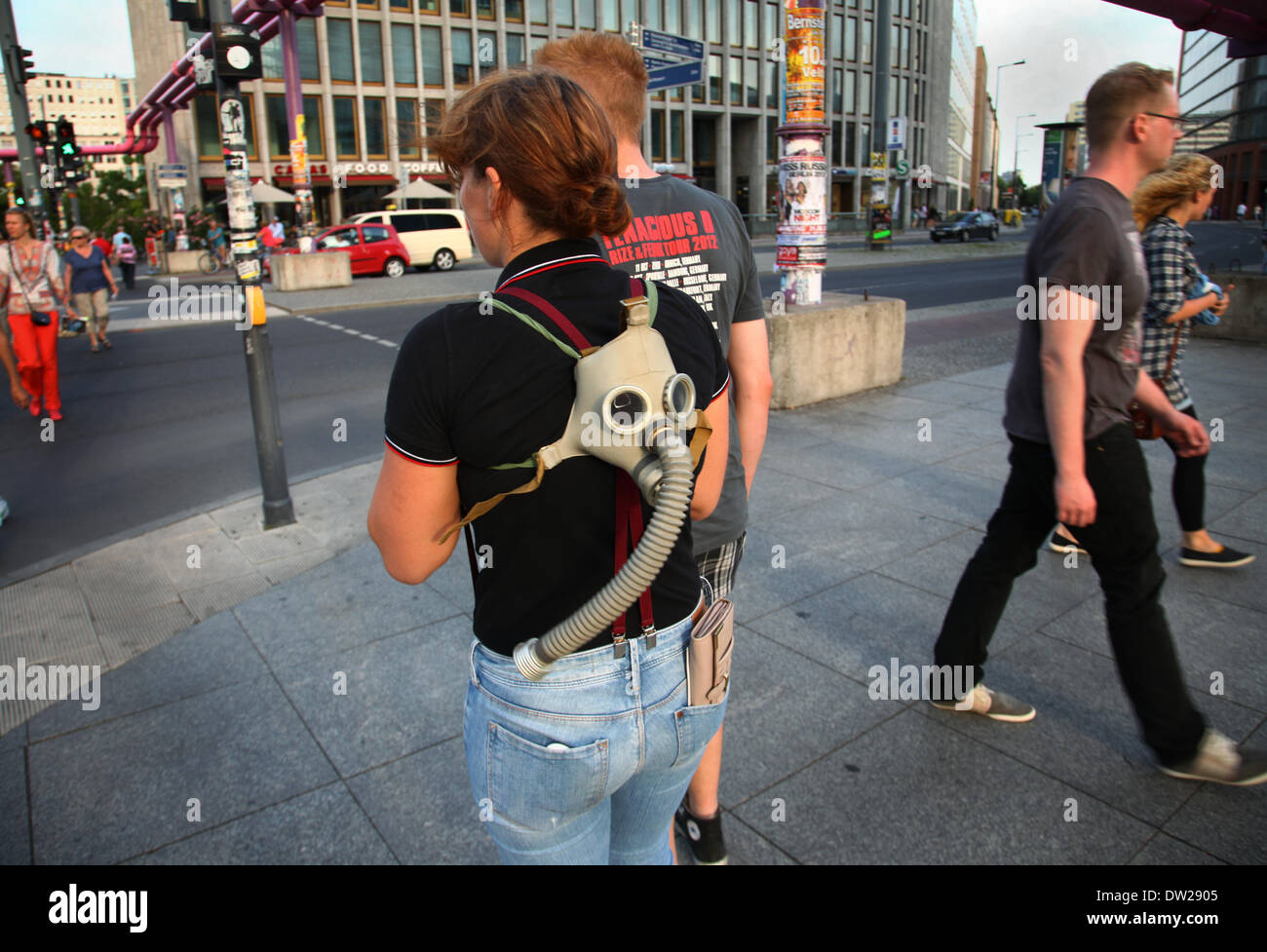 A German tourist carries a gas mask at Potsdamer Platz in Berlin, August 08, 2013. More and more tourists come to the German capital every year. The photo is part of a series on tourism in Berlin. Photo. Wolfram Steinberg dpa - Stock Image