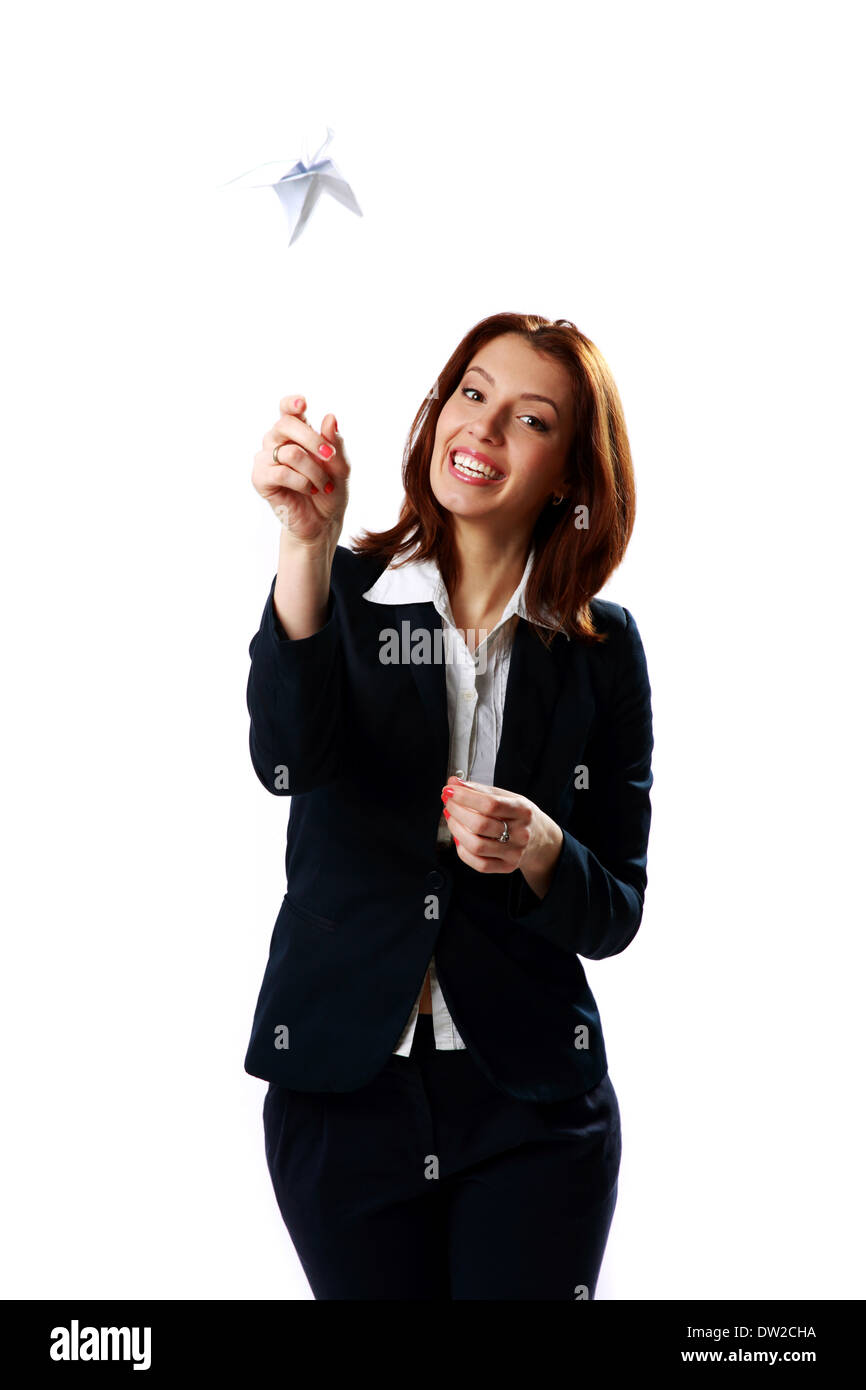 Cheerful businesswoman throwing paper plane isolated on a white background - Stock Image