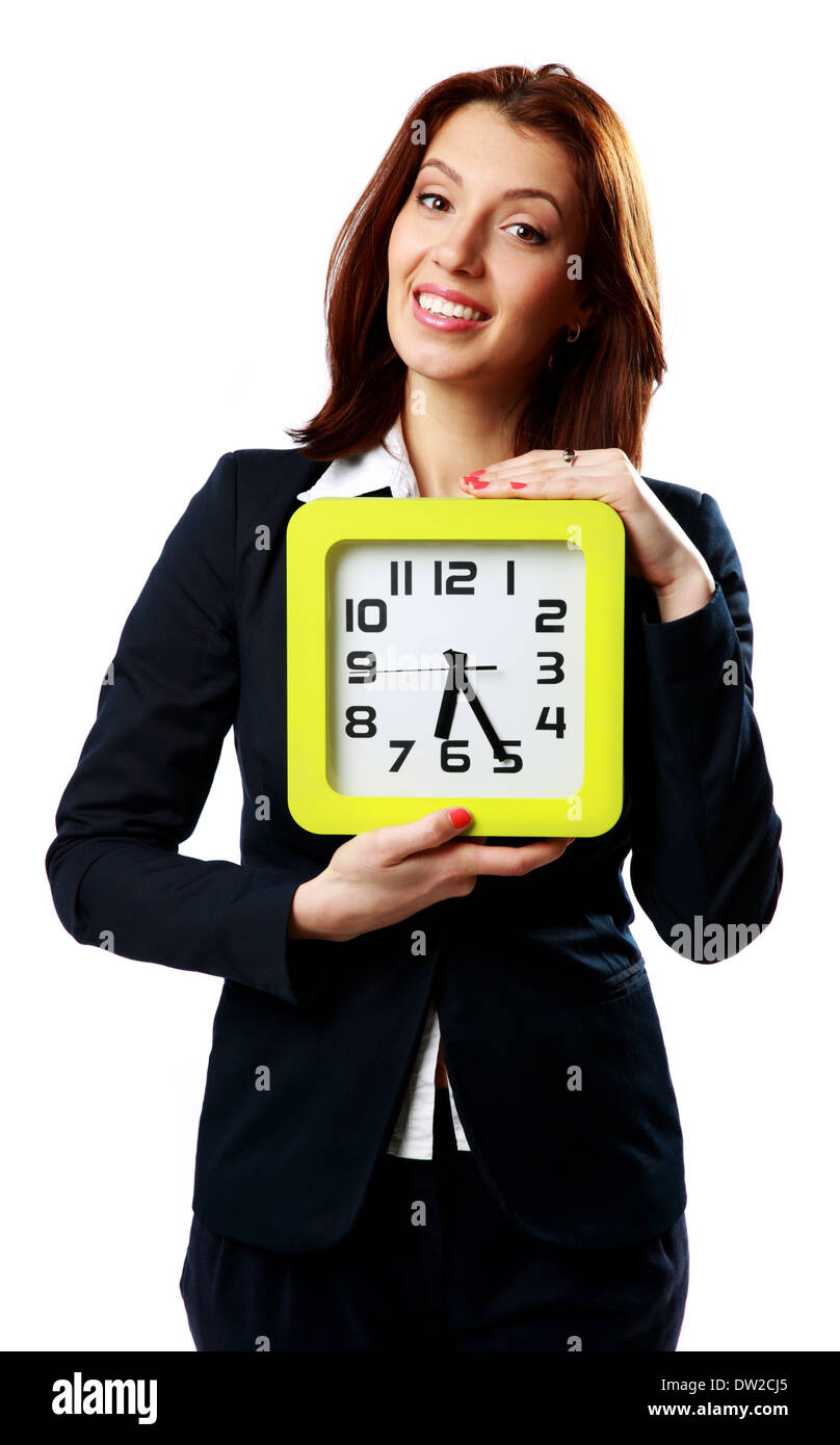 Smiling businesswoman holding wall clock isolated on white background - Stock Image