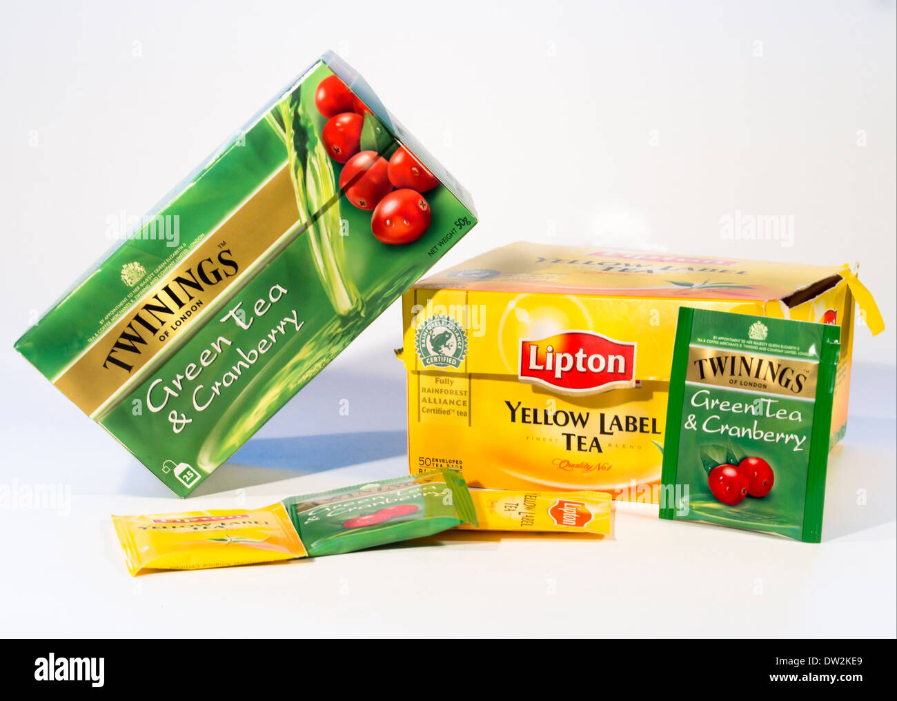 Lipton or Twining, black tea or green tea, yellow or green boxes and teabags on white background - Stock Image