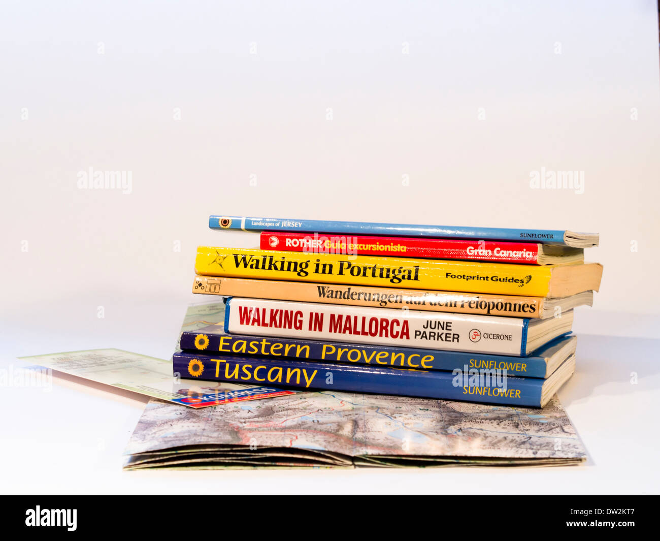 Map and stack of books for hikes in different European countries, available in many languages - Stock Image