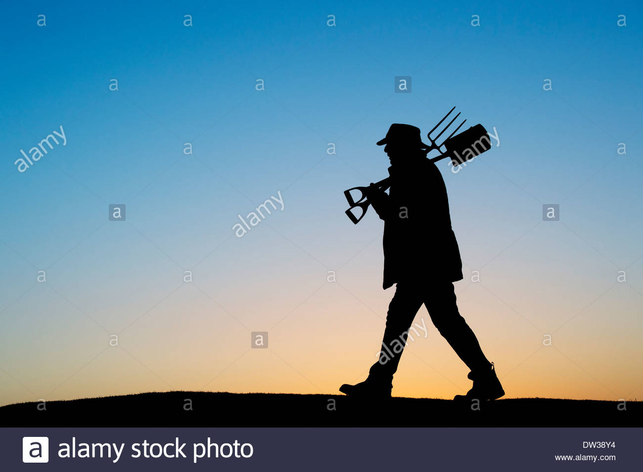 Gardener walking with spade and fork. Silhouette - Stock Image