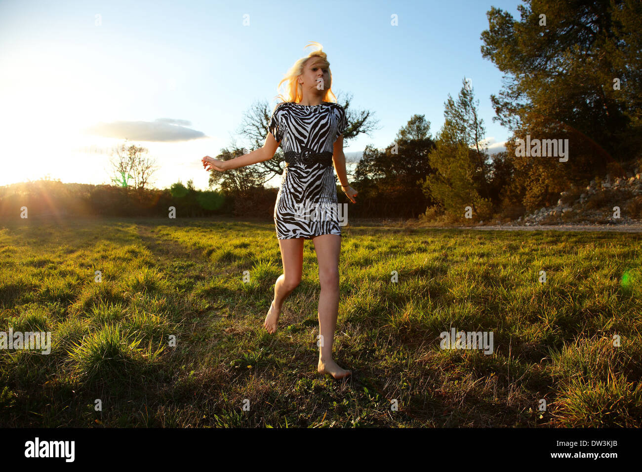 beautiful young woman running barefoot in meadow wearing a black and white zebra dress at dusk - Stock Image