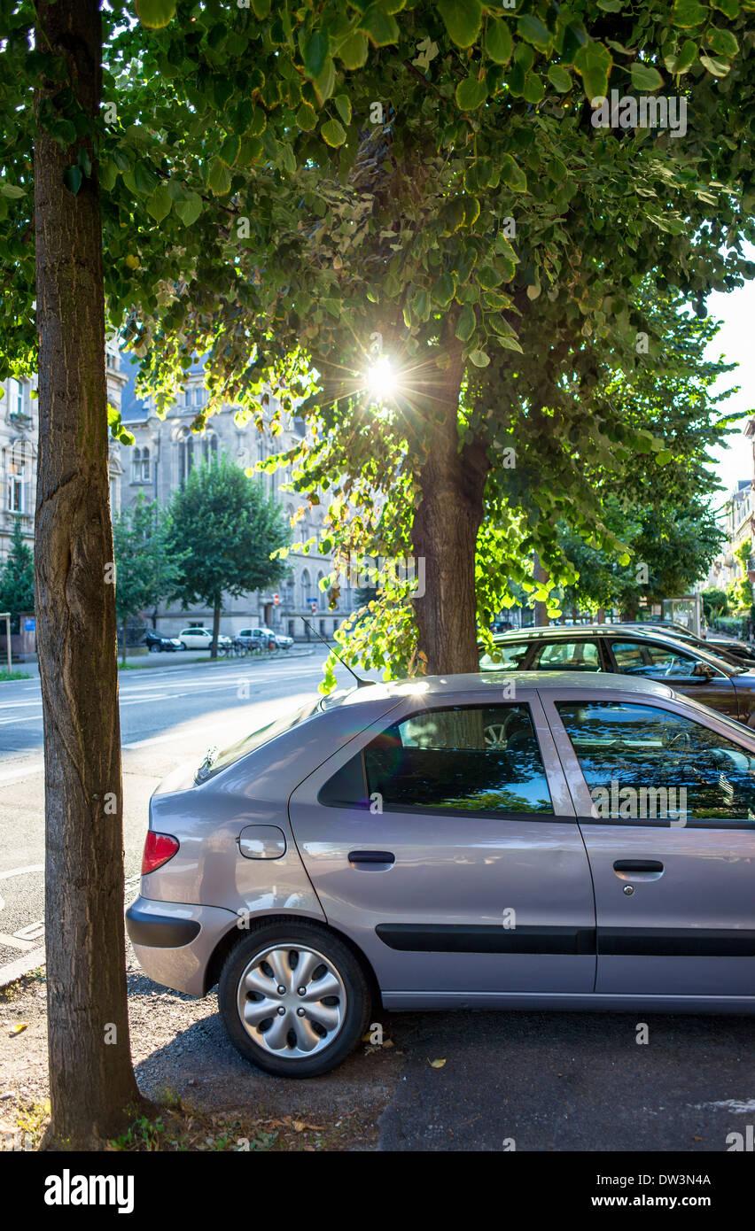 Cars parked on pavement Strasbourg Alsace France - Stock Image