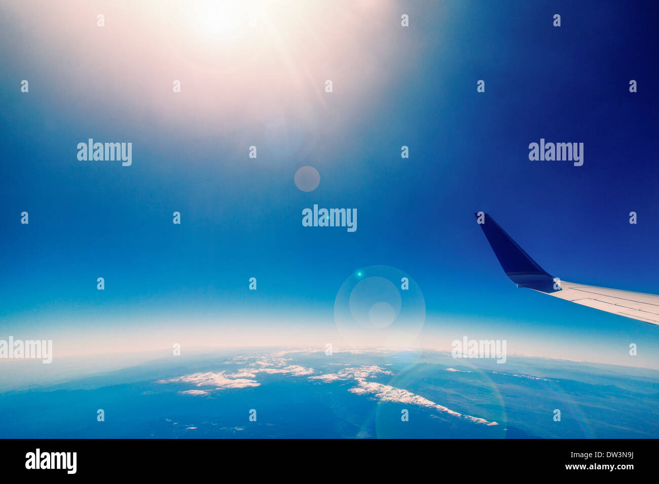 Airplane wing over curved earth - Stock Image