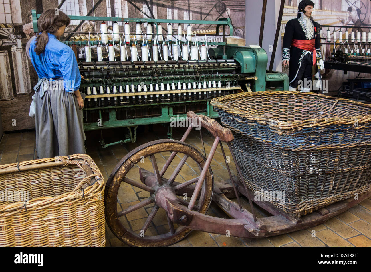 Nineteenth century English ring spinning frame and old wheelbarrow at MIAT, industrial archaeology museum, Ghent, Belgium - Stock Image
