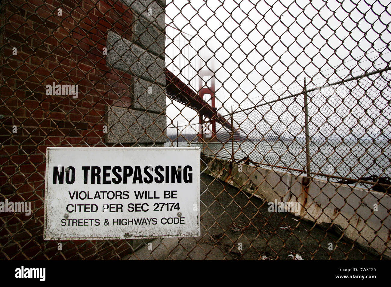 Wire netting with no trespassing signal with the Golden Gate Bridge on the background - Stock Image
