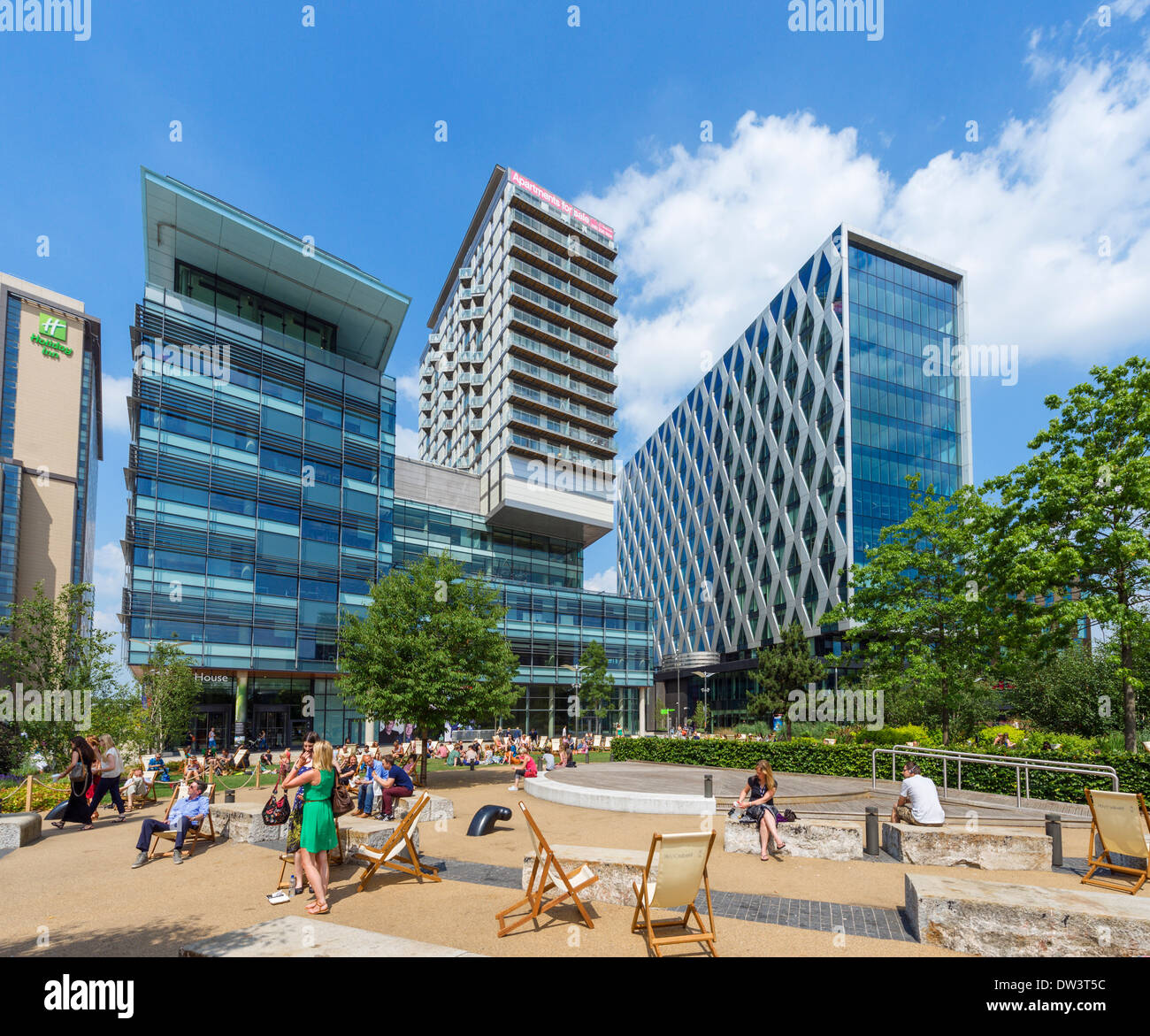 People having lunch outside apartments and offices near the BBC studios in MediaCityUK, Salford Quays, Manchester, England, UK - Stock Image