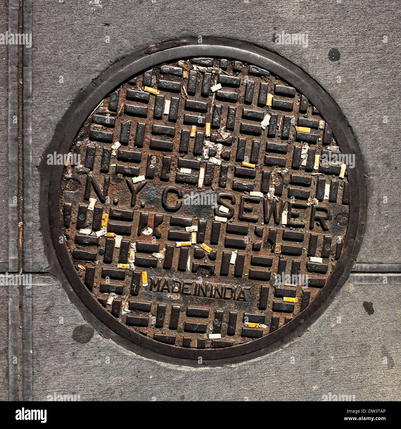 Various cigarette butts set in the grooves of an NYC sewer lid on 6th Avenue in Manhattan. - Stock Image