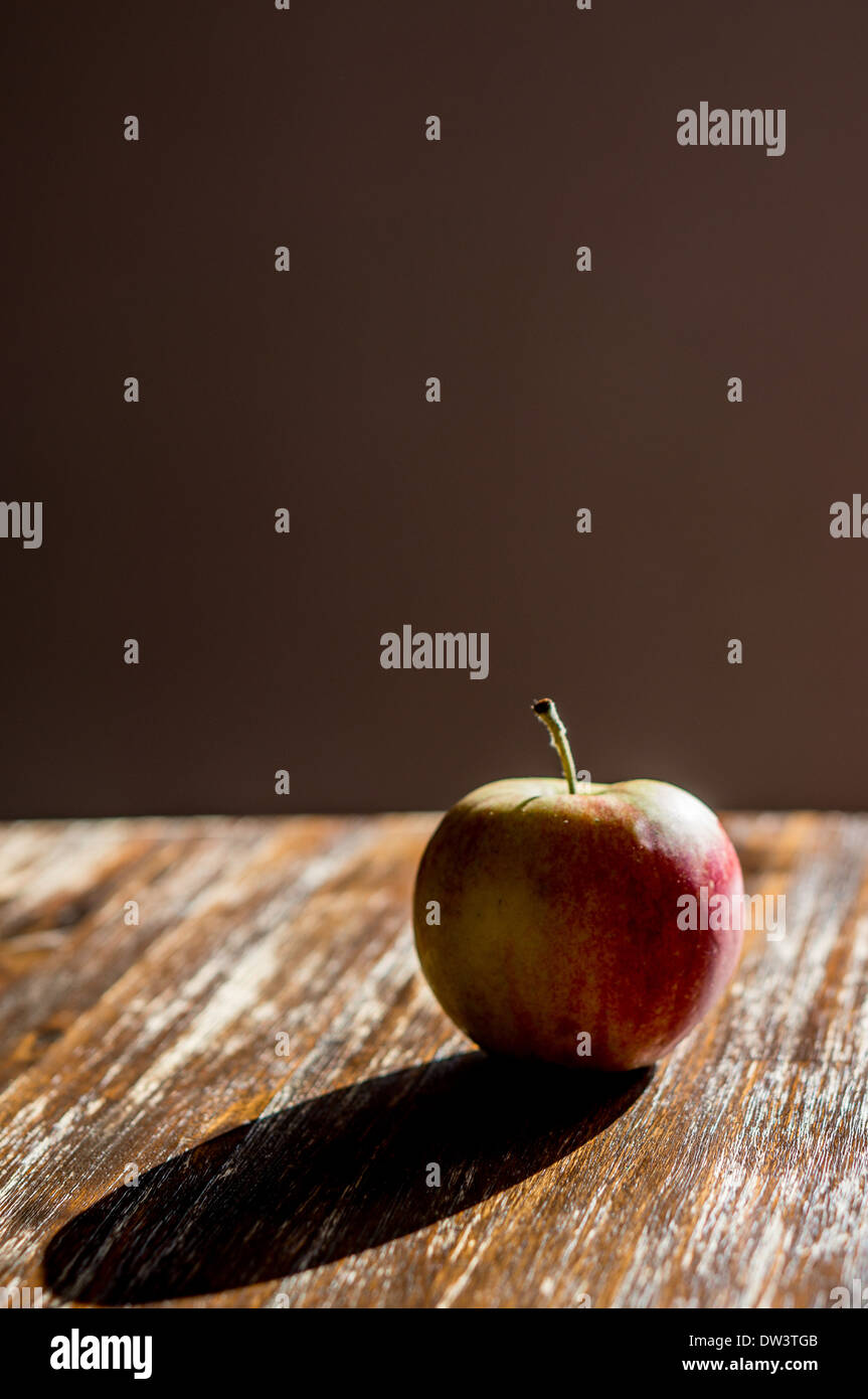 A solitary apple on a table with a plain background - Stock Image