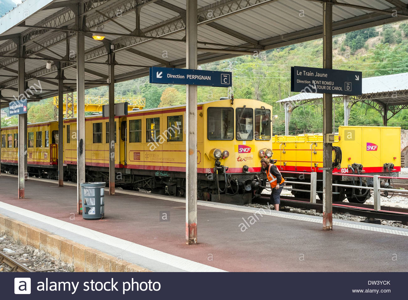 A worker inspects the Train Jaune (Yellow Train) at the station in Villefranche-de-Conflent, before departure. - Stock Image